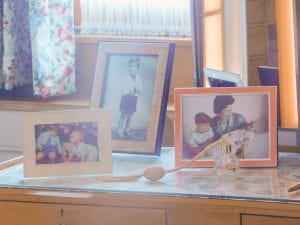Photos of the Queen, her children, and her perfume on her dresser.
