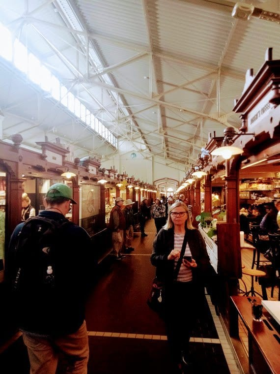 Inside Hakaniemi Market Hall people shop for traditional Finnish Food.