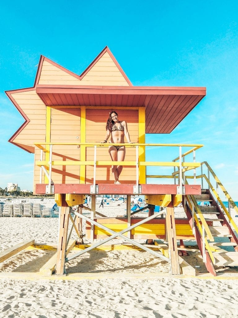 Sarah Fay travel blogger on a colorful red and orange lifeguard stand on South Beach Miami.
