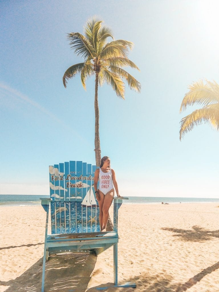 Sarah Fay travel blogger getting sun on a giant Adirondack chair on Fort Lauderdale Beach.