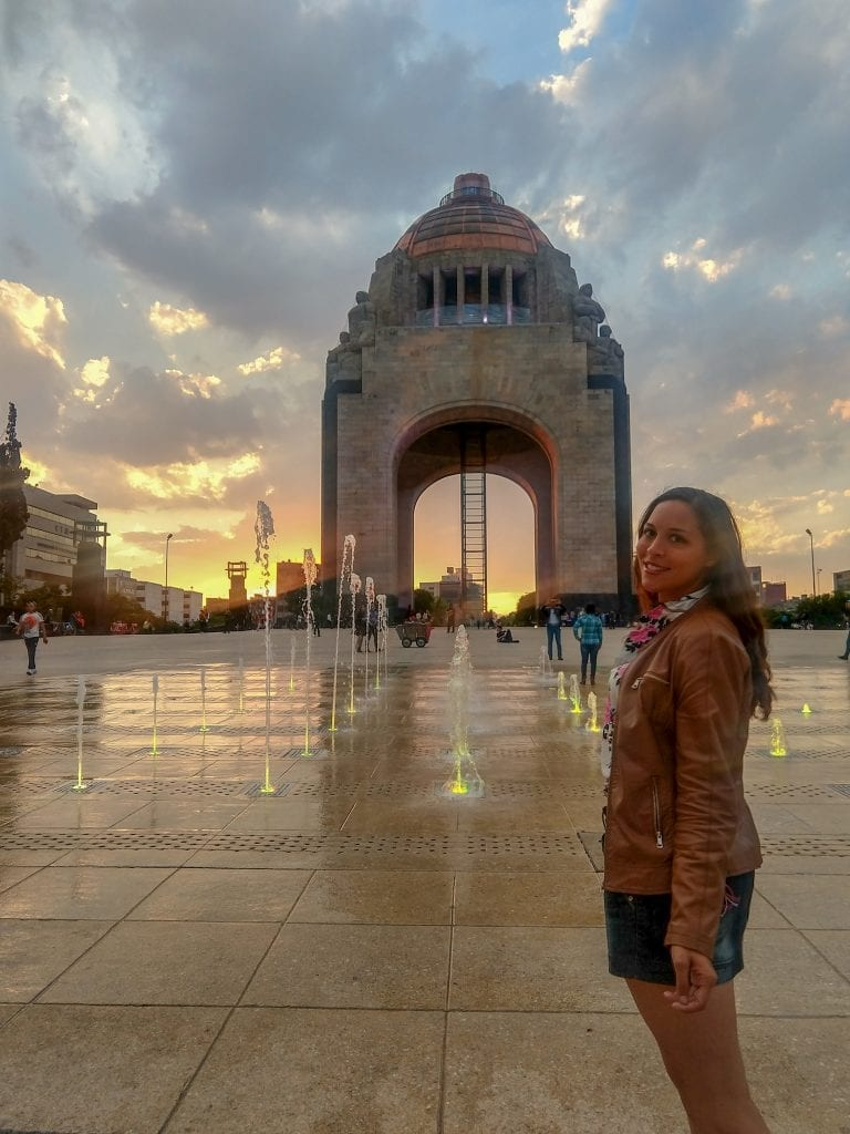 Sarah Fay enjoying the sunset in Mexico City at the Monumento a La Revolucion standing in front of a fountain.
