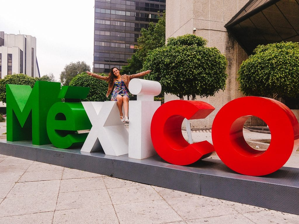 Sarah Fay travel vlogger sitting on Mexico sign in mexico city.