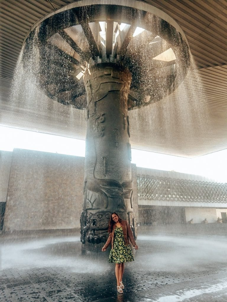 Sarah Fay at the Anthropology Museum in Mexico City in front of waterfall like fountain.