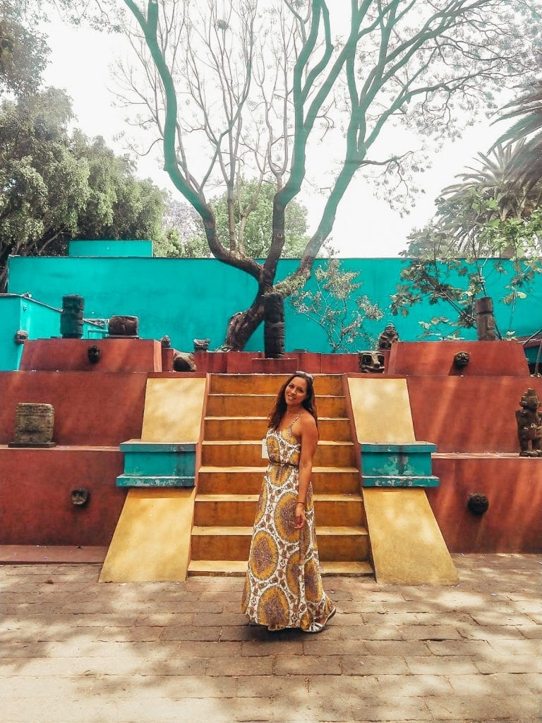 Entrance to Frida Kahlo's Museum in Mexico City in colorful garden travel blogger poses.