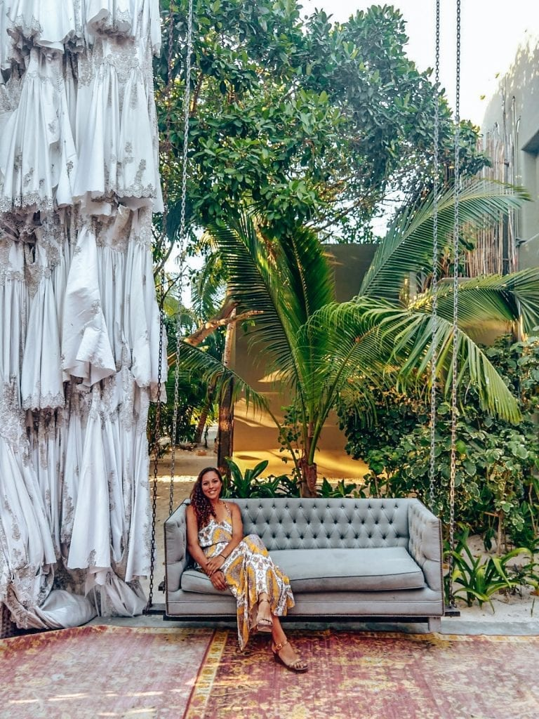 Sarah Fay travel blogger in couch swing at Casa Malca Pablo Escobar's old house now hotel in tulum Mexico.