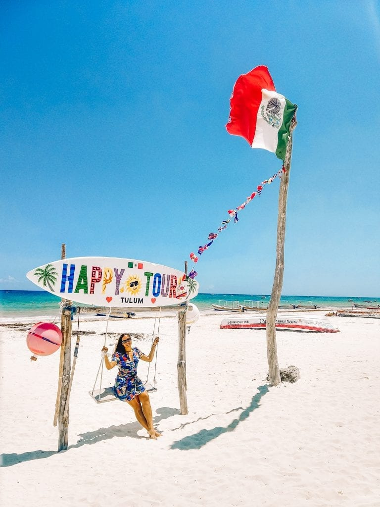 Sarah Fay travel blogger on the Happy Tulum swing on Tulum Beach with a Mexican flag flying in the air on a sunny day.