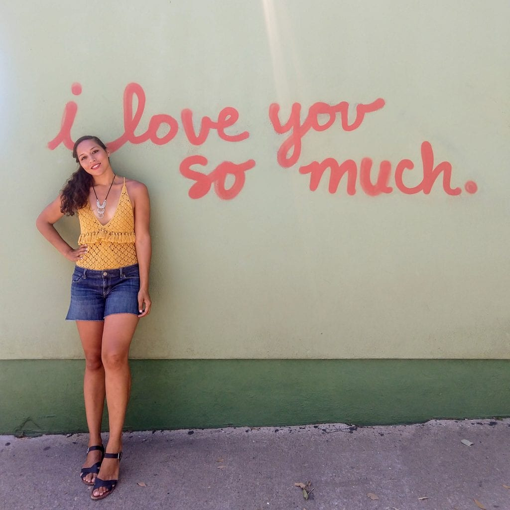 I love you so much mural in Austin Texas Sarah Fay IN FRONT OF IT.