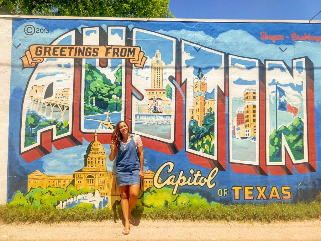 Sarah Fay in Austin Texas in front of mural of a Postcard from Austin Texas. Girls Getaway weekend to Austin, Texas