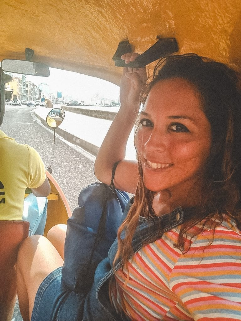 Supporting a local in Cuba by riding in their pedi cab in Havana.