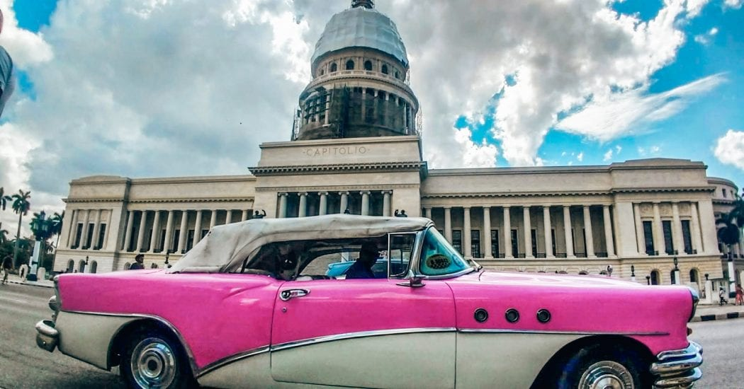 Old School pink 1960s car in front of the Cuban Capitol building in Havana ,Cuba.