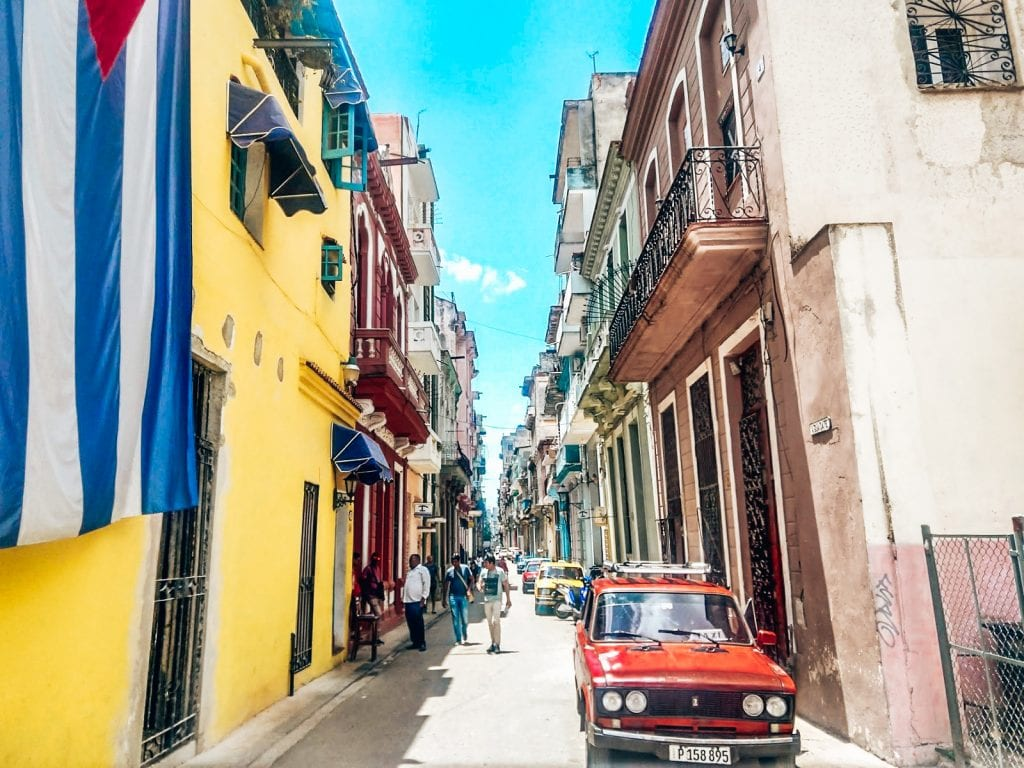 Old colorful street in Havana, Cuba with the cuban flag on the left and an old car on the right.The streets in old havana were interesting and easy to explore as a solo traveler.  #CUBA