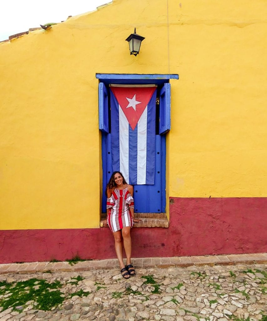 Sarah Fay sitting on ledge in front of bright colored building and Cuban Flag in Trinidad Cuba.