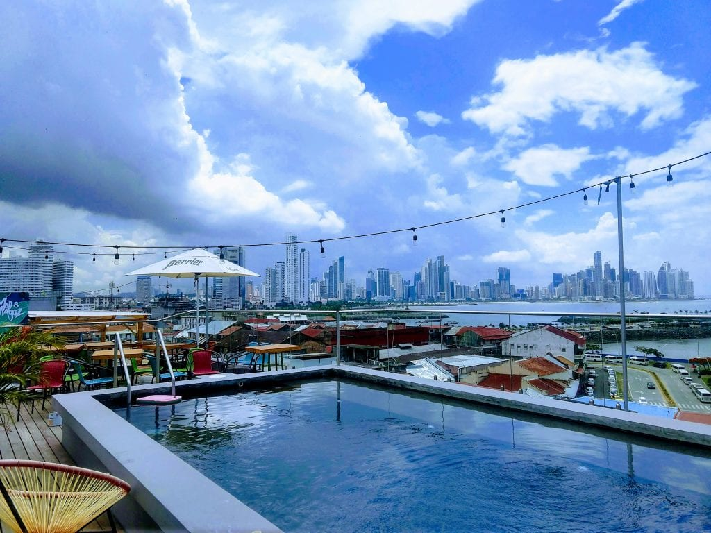 Selina Hostel roof top pool and bar overlooking the skyline of Panama City, Panama on a sunny day with blue skies.