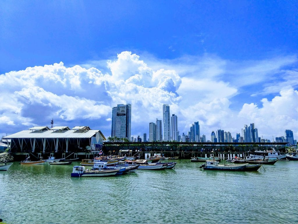 Market for fish in Panama City, fisherman are pulling boats up to the market with the skyline of Panama City towering behind.