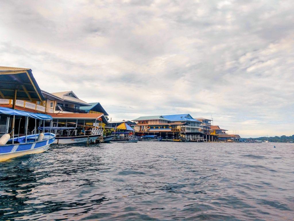 Bocas Del Toro from the water has many hotels, restaurants, and water taxis along the waterfront in Bocas Town on the main island of Colon. Colorful buildings dot the landscape and make for a beautiful scene from the water. #Visitpanama #bocasdeltoro