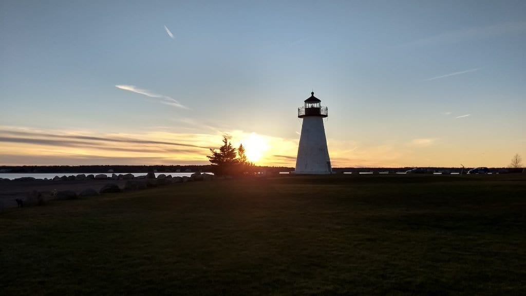 Lighthouse in New England during sunset with ocean in background.