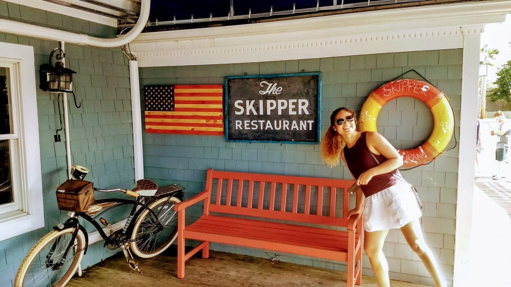 Girl in front of sign for Skipper Restaurant in Yarmouth on Cape Cod Massachusetts.