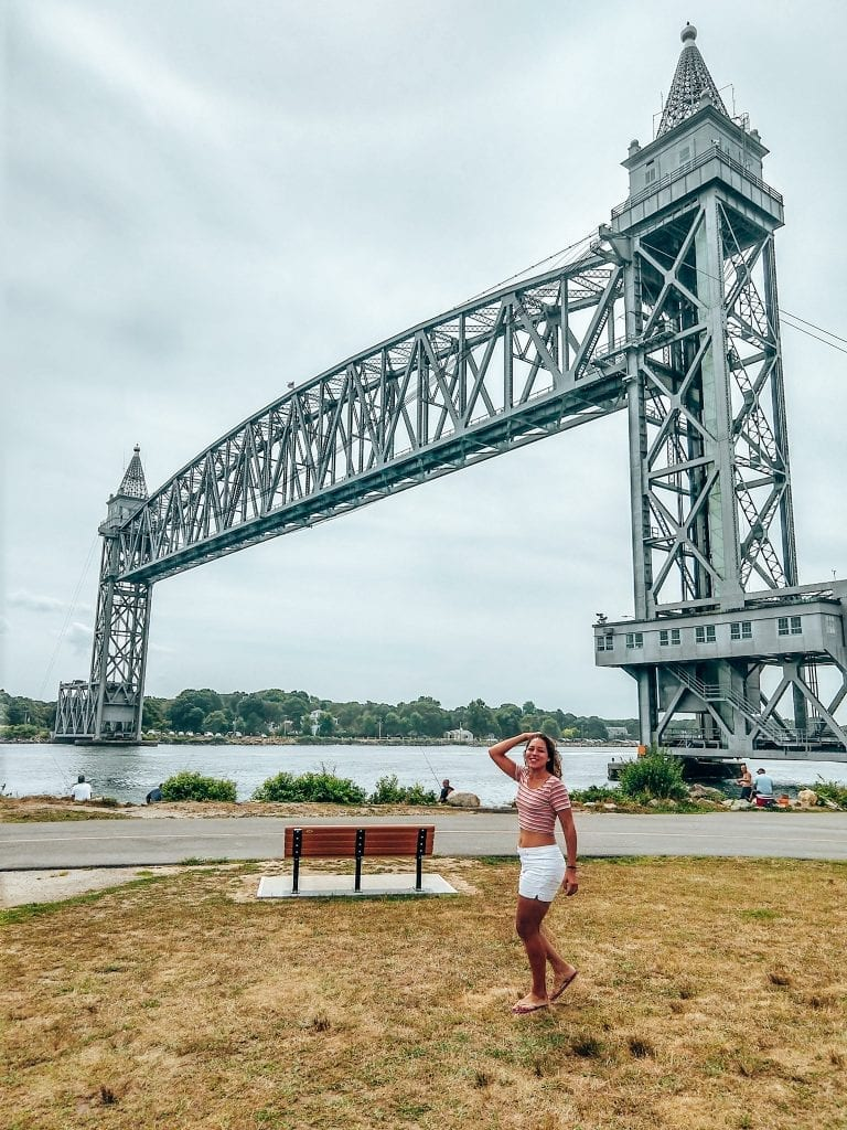 Sarah Fay travel blogger in front of the Cape Cod Canal Rail road bridge  in Massachusetts, USA.