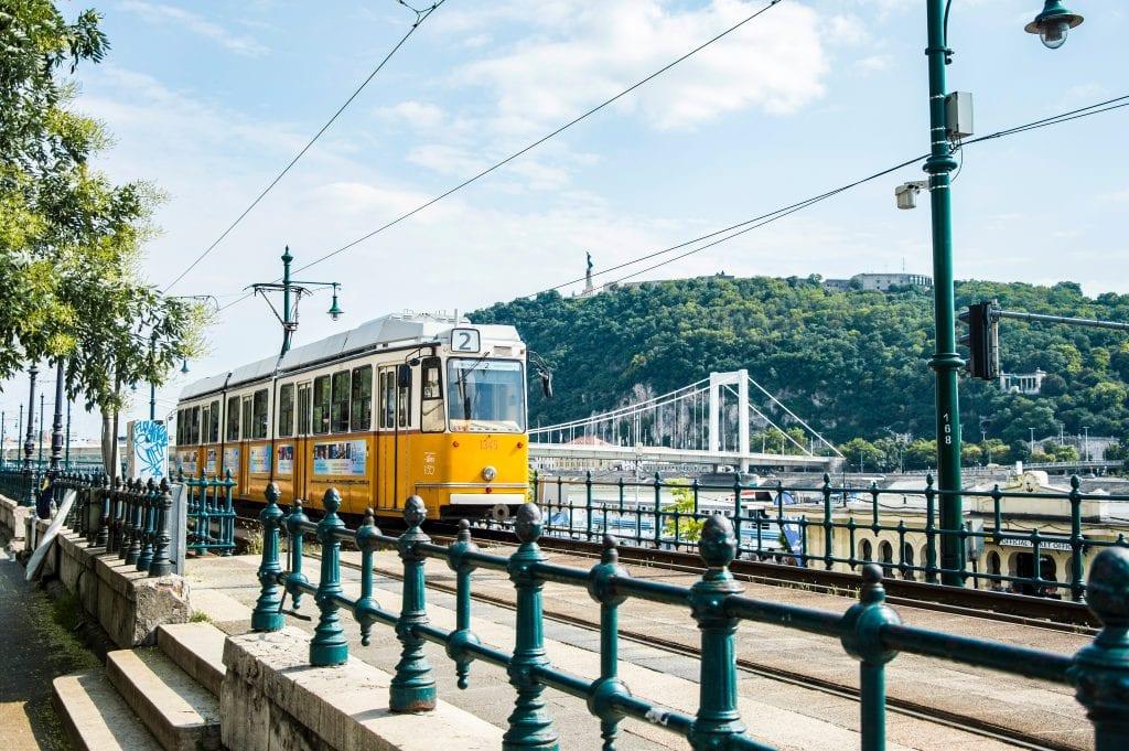 A tram goes along side the Danube in Budapest Hungary. #visitbudapest #budapesttravelguide