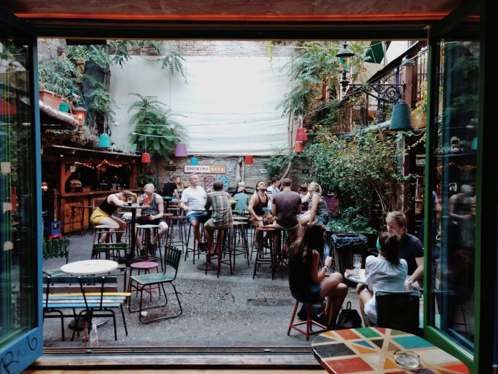 People sit and enjoy the day at a ruin pub in budapest Hungary  in a courtyard. #ruinbar #budapest