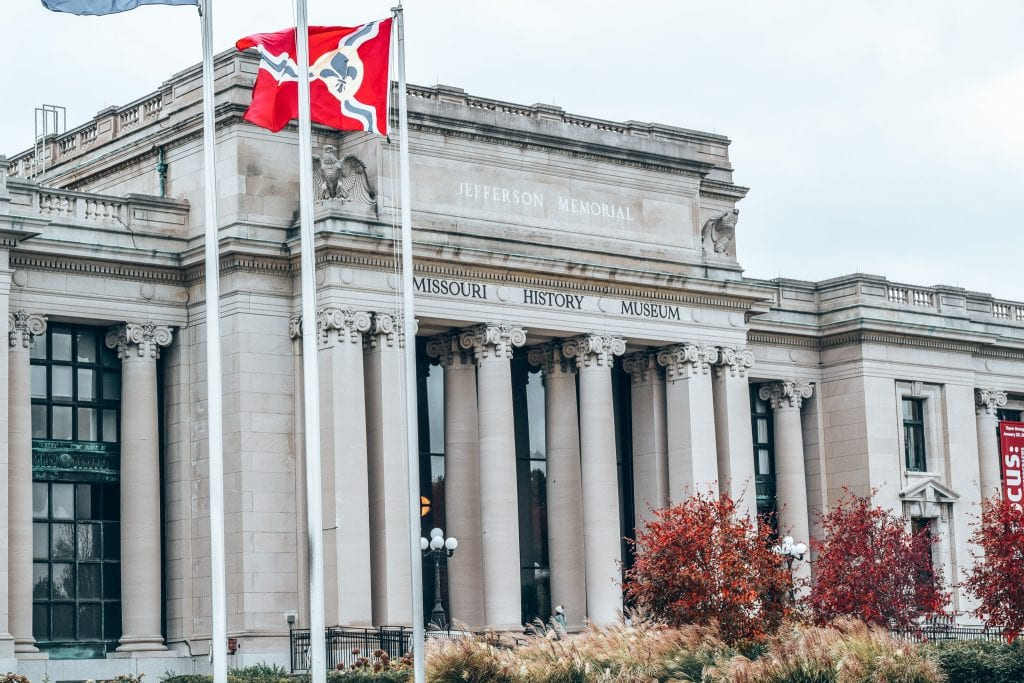 The Missouri History Museum on a grey day with the flags waving in front and fall foliage.   #visitmissouri #saintlouis