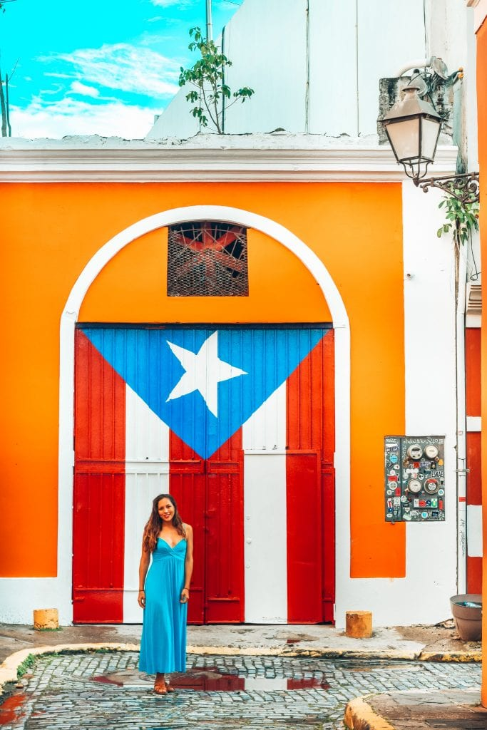 Travel Blogger Sarah Fay in long blue dress in front of doorway painted with Puerto Rican flag in Old San Juan. Exploring the street art in Old San Juan and the colorful buildings. #discoverpuertorico #oldsanjuan