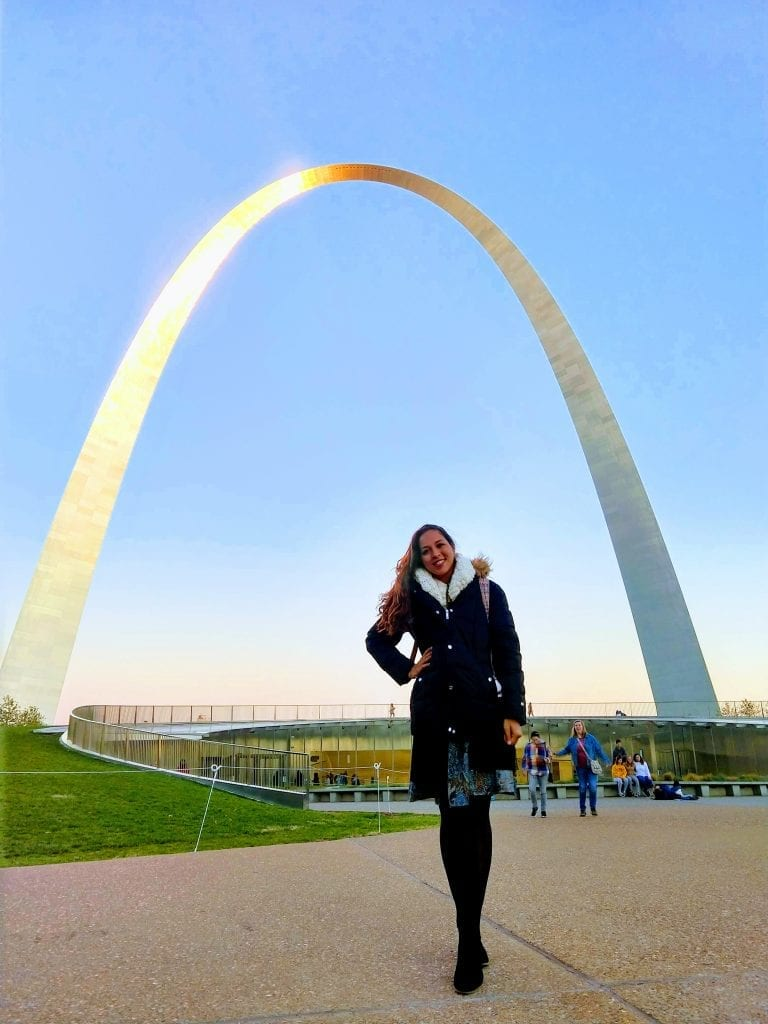 Sarah Fay standing with her hand on her hip infront of the Gateway Arch National park on a sunny day.   #visitsaintlouis #explorestlouis