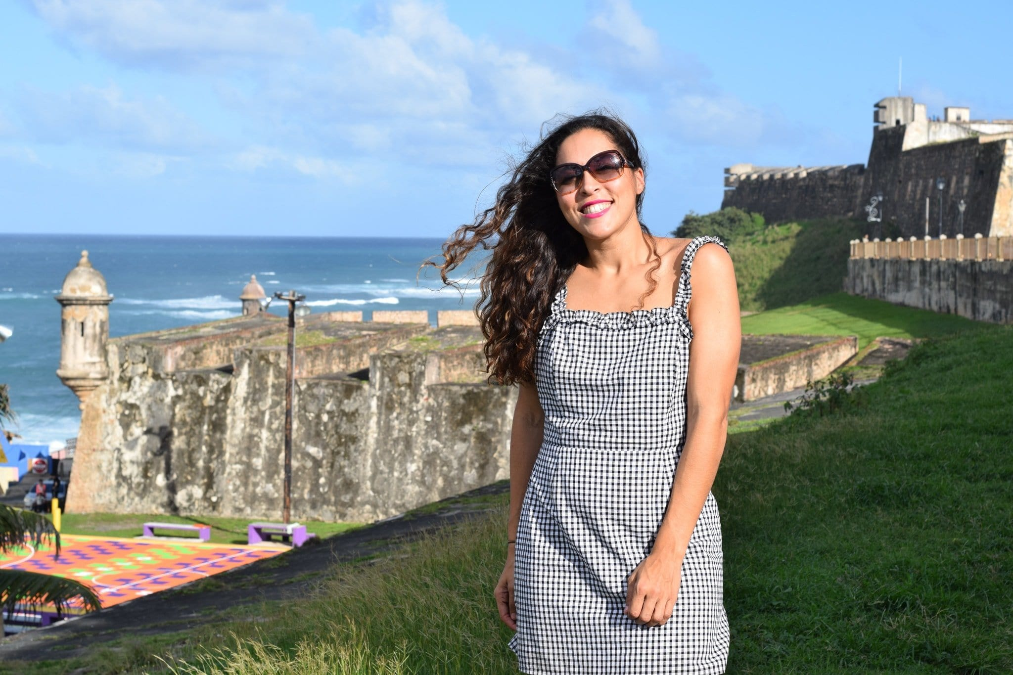 Sarah Fay Solo Travel blogger in old San Juan at Castillo San Cristóbal with the La Perla neighborhood basketball court in background.