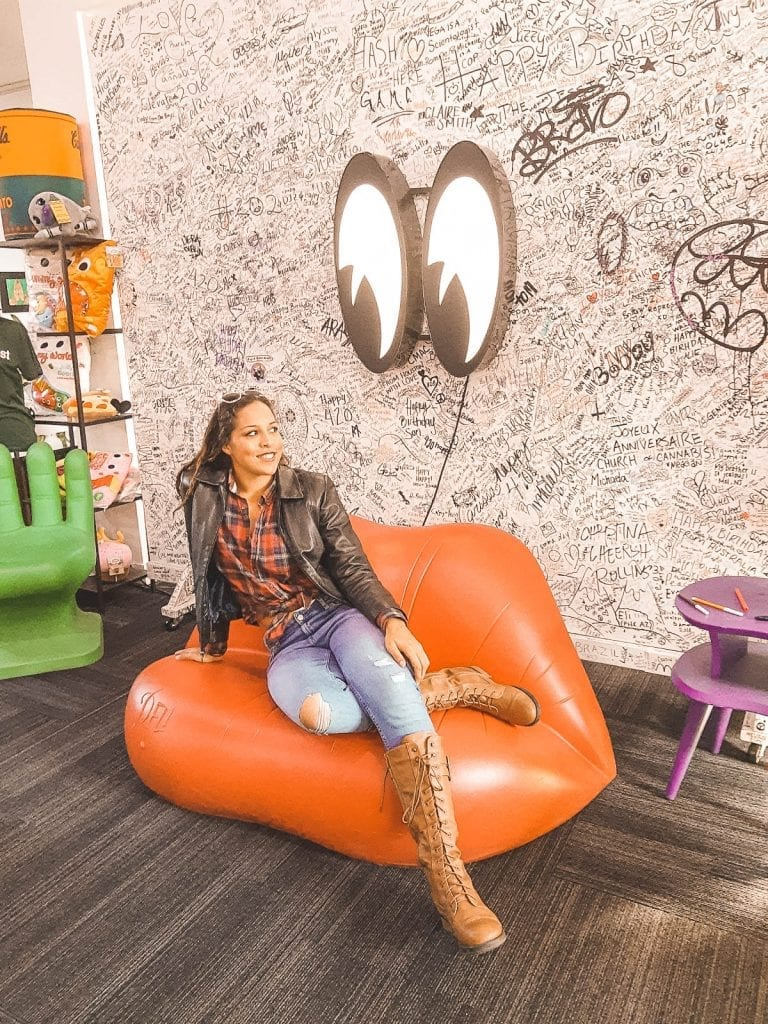 Sarah Fay travel blogger Chilling in the hangout area of the International Church of Cannabis in Denver, CO sitting on a couch that looks like lips in front of a wall that everyone signs.