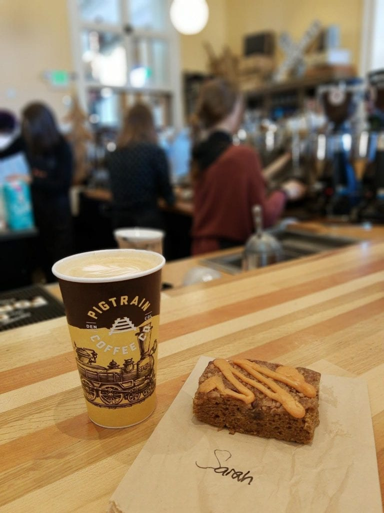 Pig Train Coffee in Union Station Denver Colorado. A large latte and coffee cake sit on the counter while the baristas make drinks.