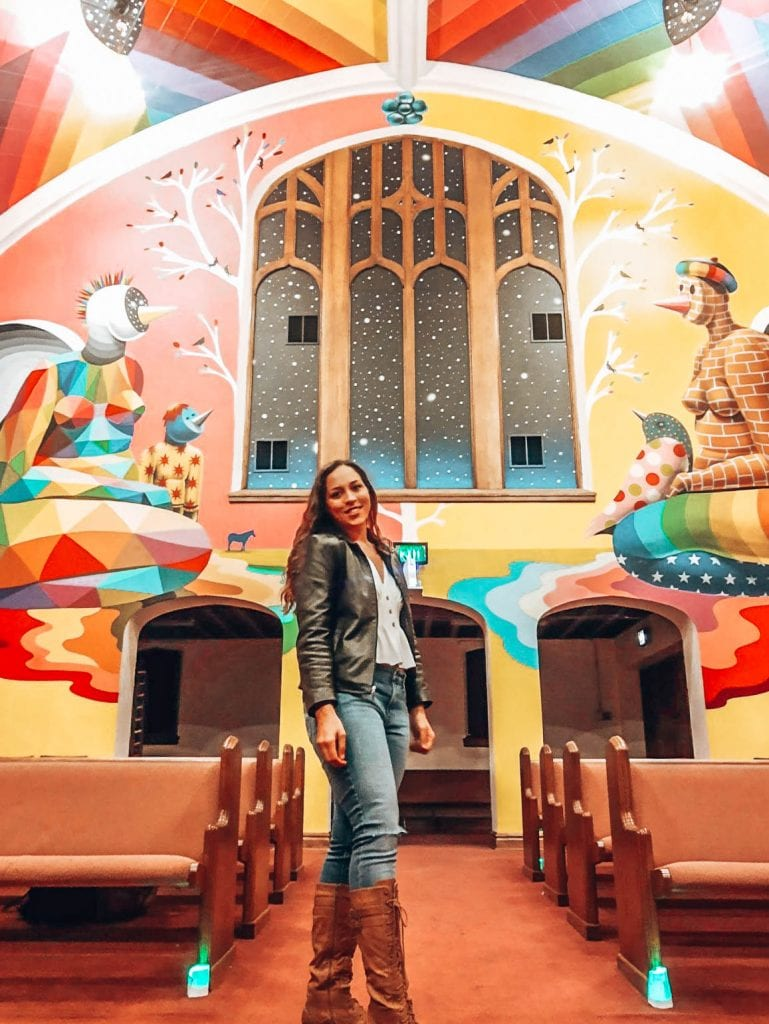 Sarah Fay inside the International Church of Cannabis in front of the very bright wall art inside this Denver, Colorado attraction!
