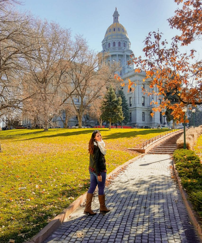 Sarah Fay walking towards the Denver State Capitol Building with fall leaves on the ground and in the trees.