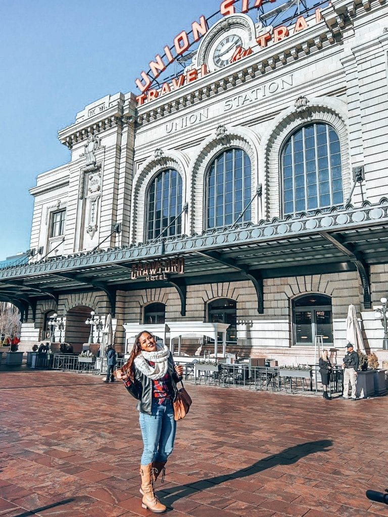 Sarah Fay in front of the Union Station in Denver Co in a flannel shirt and jeans with a leather jacket.