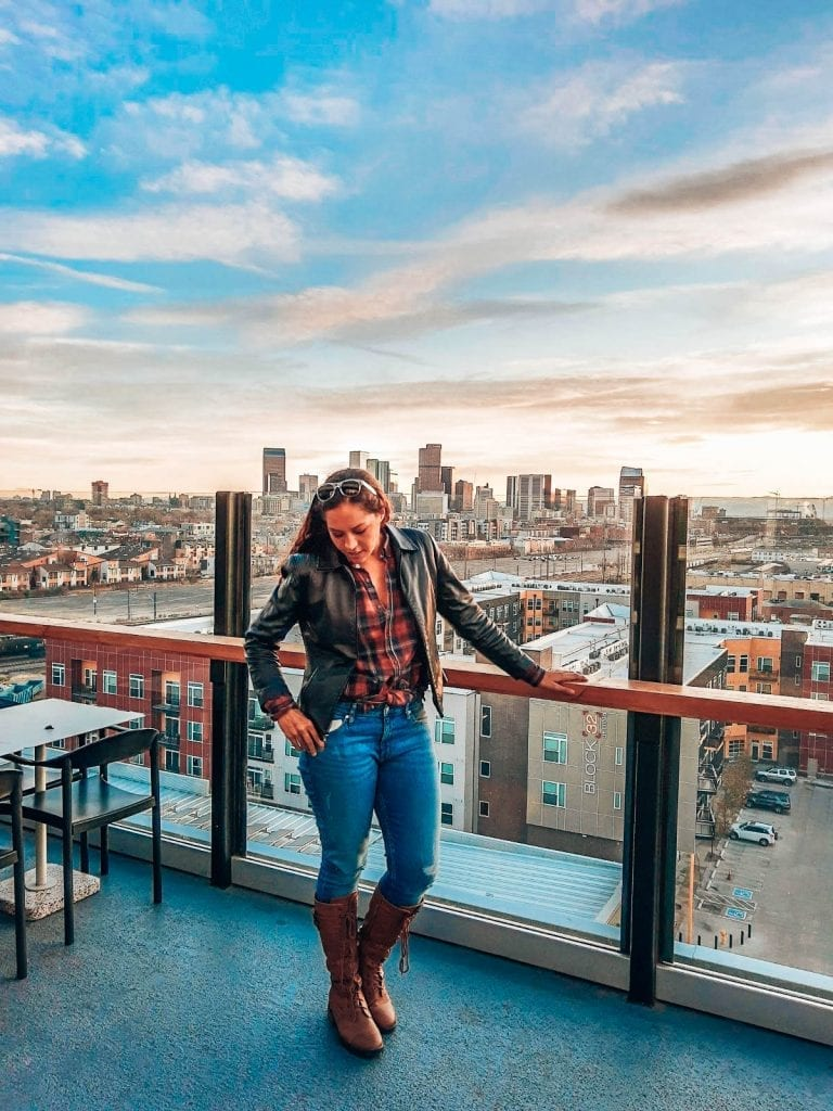 Sarah Fay looking down, while watching the sunset at The Source Rooftop in Denver, Colorado with the city skyline in the background.
