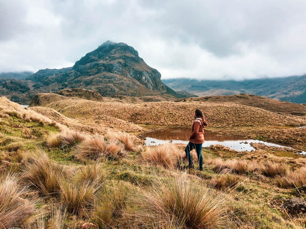 Cajas National Park near Cuenca, Ecuador. Sarah Fay standing in the field of Cajas with a small lake near her. #visitecuador
