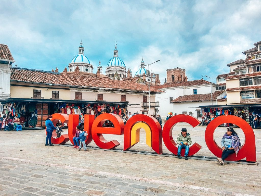 Cuenca Ecuador sign in the middle of a square with the Cuenca Cathedral roof top in the background on a cloudy day. #cuenca #visitecuador