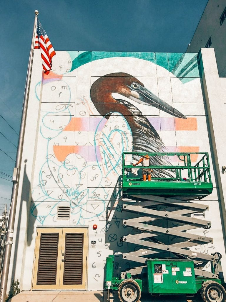 Woman graffiti artist and street muralist painting huge mural on wall of building on a lift in Wynwood, Miami during Art Basel.
