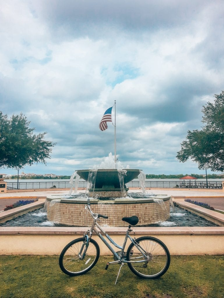 Bike with kickstand up and the American flag flying in the background behind a fountain with Lake Baldwin in the back. One of the best bike trails in Orlando.