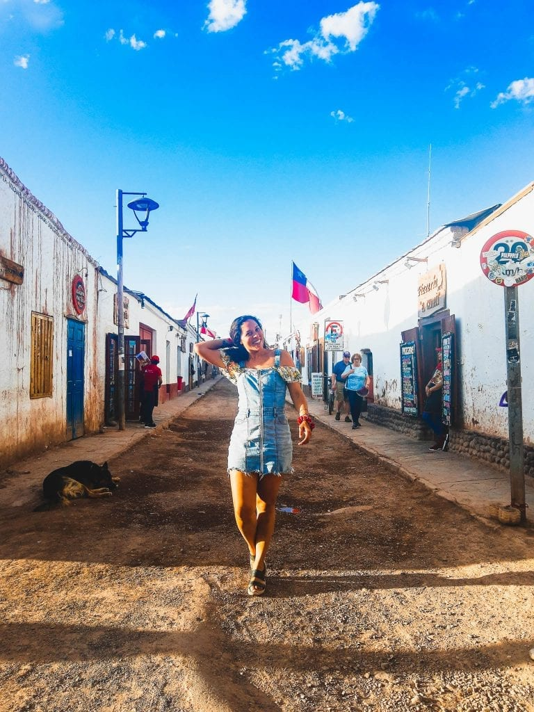 San Pedro de Atacama, Chile- A beautiful historic town with dirt roads and low laying buildings. Travel blogger Sarah Fay walking down the street.