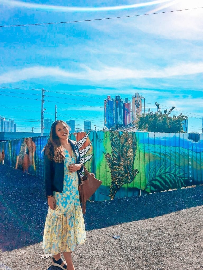 Sarah Fay travel blogger standing in front of abandoned warehouse area with street art and graffiti everywhere. Art Basel Miami Beach.