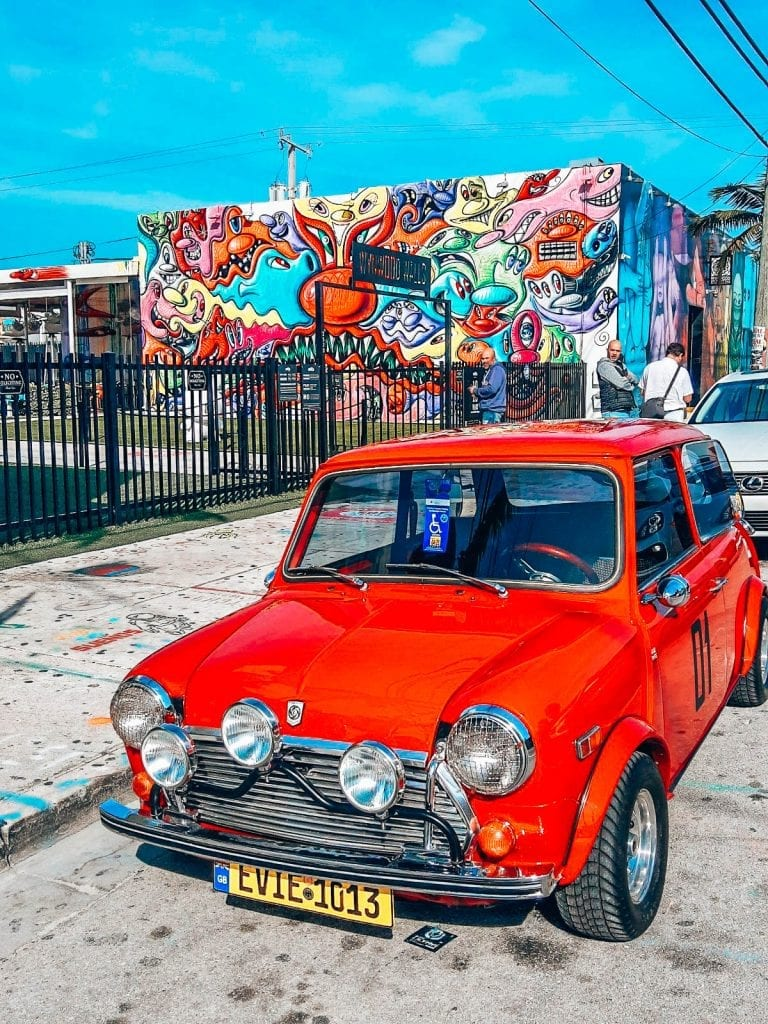 Wynwood Walls during Miami Beach Art Basel with a red mini cooper parked out front.