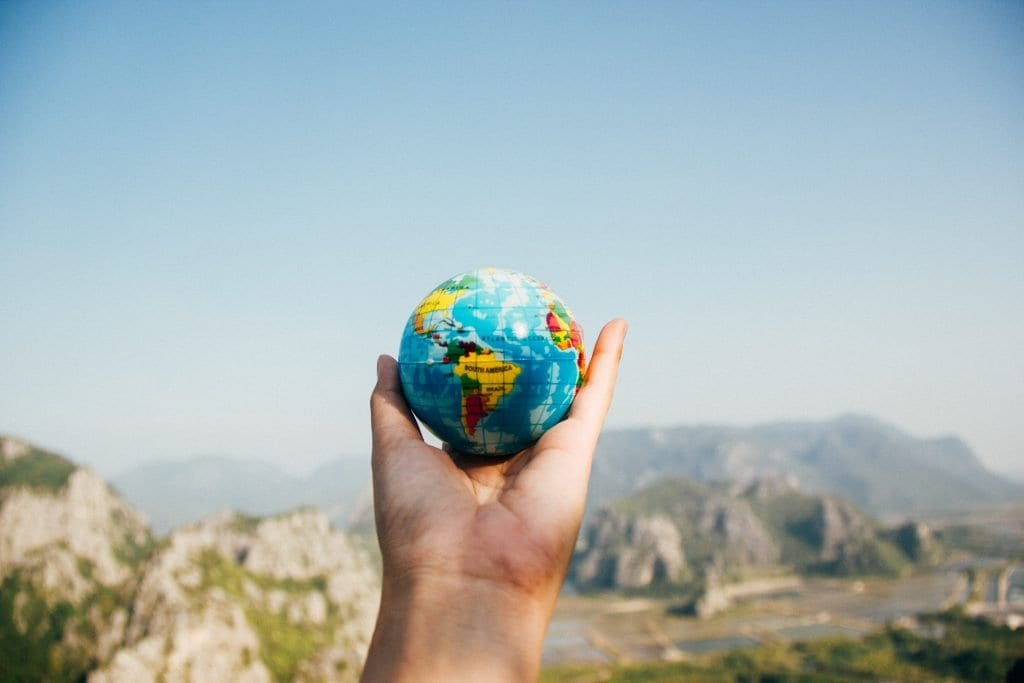 A small globe being held in a hand in front of a landscape of mountains.