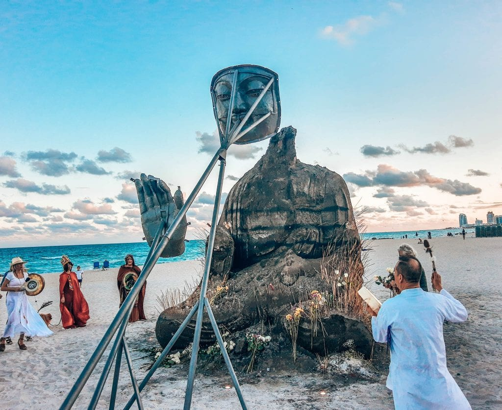 People gathering around the budha on the beach at the Faena for the closing ceramony of Art Basel Miami Beach.