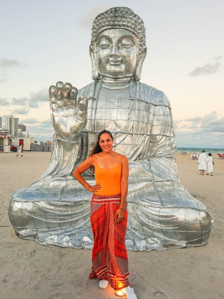 Sarah Fay in front of huge Budha at Faena Festival in Miami Beach during Art Basel.