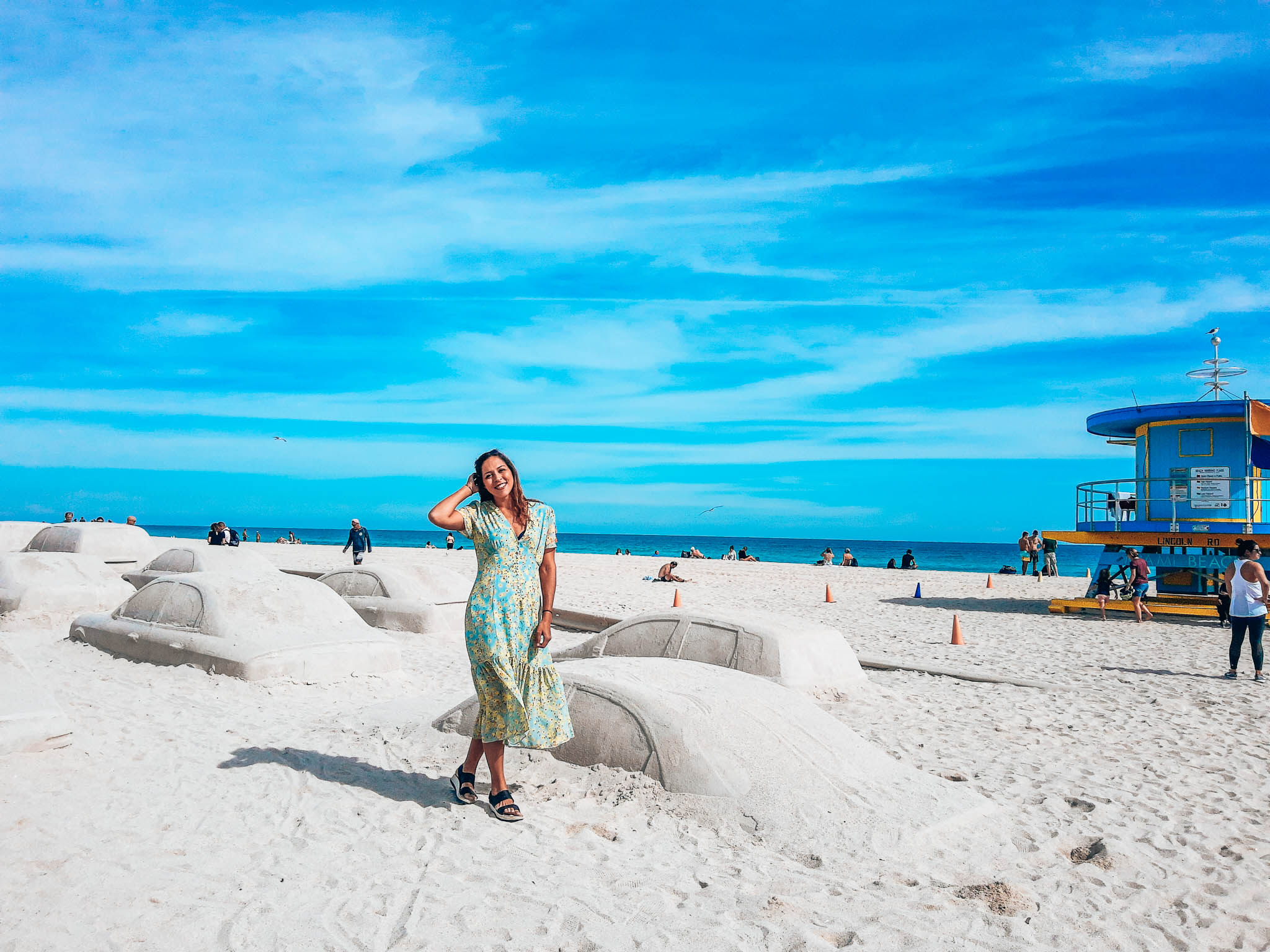 Sarah Fay infront of Sand sculptures of taxis made in sand. Art Basel Installation on beach.
