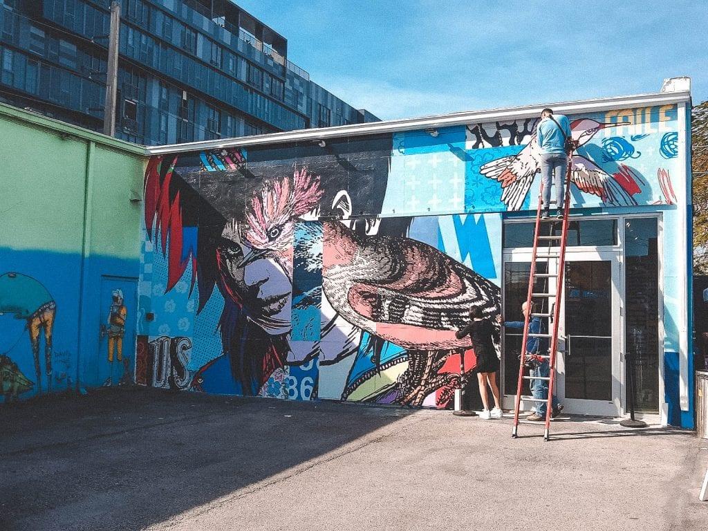 Artists working on huge mural at Wynwood Walls during Art Basel week in Miami.