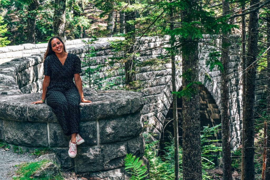 Acadia National Park in Maine. Sarah Fay sitting on one of the many carriage road stone bridges.