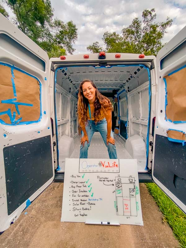Check list for getting started on a van life van build. Sarah Fay is standing up in her van with white board plan in front of her.