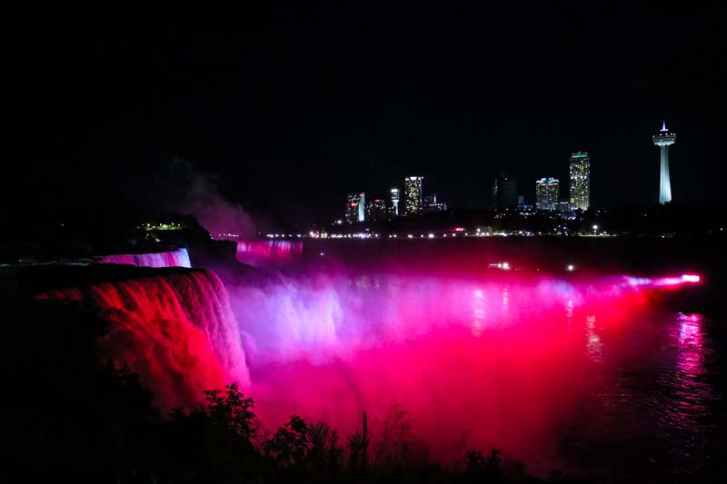 Niagara Falls lit up at night red with Niagara Falls Canada in the background taken from Niagara Falls State Park.