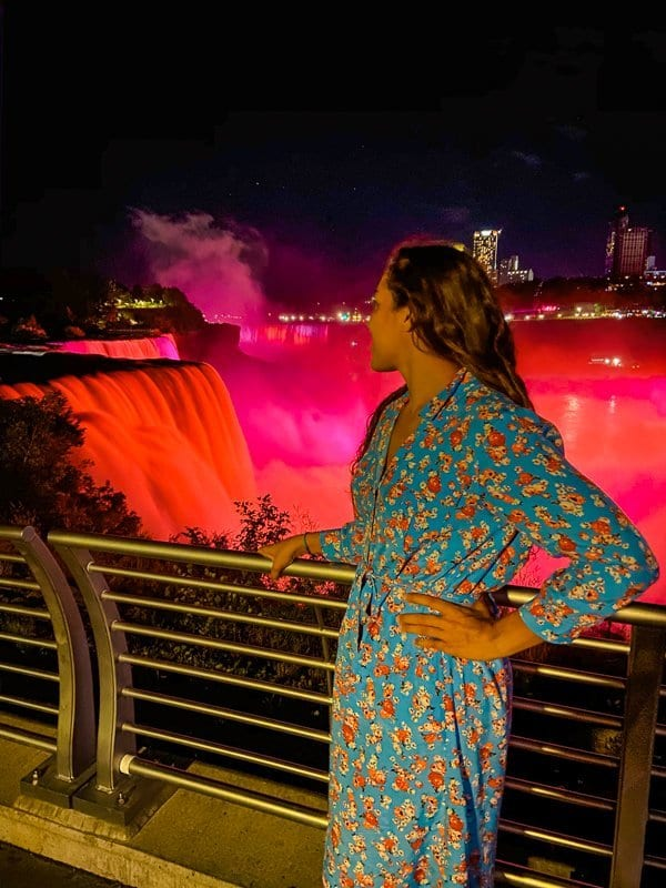 Sarah Fay travel blogger, in front of Niagara Falls on the US Side of Niagara Falls. Niagara Falls lights up at night. Prospect Point viewing area offers the best views of Niagara Falls at Night or Day.